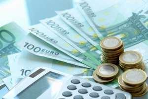 Ein Taschenrechner, viele Euromünzen und Geldscheine stehen hier für Steuern