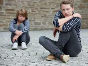 2 Mädchen sitzen unglücklich auf dem Boden