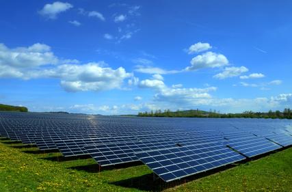 Solarkraftwerk auf satter Wiese bei schönem Wetter