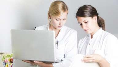 Zwei junge Ärztinennen mit Laptop und Krankenakten