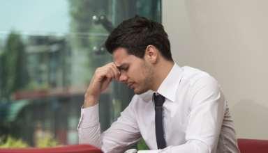 Junger Mann sitzt gestresst im Büro